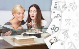 Twee vrouwen die showcase met juwelen, de achtergrond van verkoopetiketten bekijken stock fotografie