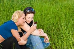 Twee vrouwen die sms lezen Stock Afbeeldingen
