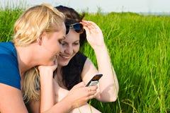Twee vrouwen die sms lezen Stock Foto's