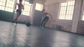 Twee vrouwen die Snelheid en behendigheids lopende boor in gymnastiek doen stock videobeelden