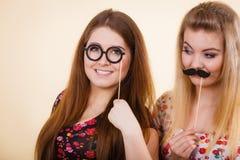 Twee vrouwen die snor en oogglazen op stok houden royalty-vrije stock foto