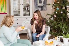 Twee vrouwen die thee drinken dichtbij een Kerstboom Moeder met dochter Royalty-vrije Stock Foto's