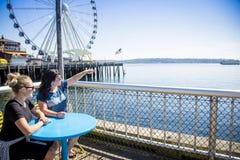 Twee vrouwen die uit de haven van Seattle op een zonnige dag bekijken stock afbeeldingen