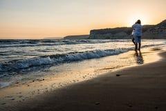 Twee vrouwen die van de zonsondergang op een strand genieten Royalty-vrije Stock Afbeeldingen