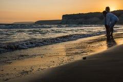 Twee vrouwen die van de zonsondergang op een strand genieten Stock Fotografie