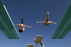 Twee Vrouwen die van Duikplanken duiken Stock Foto's