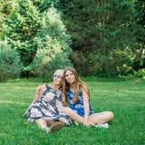Twee vrouwen die van verschillende generaties op het gras in het park zitten Moeder en dochter Royalty-vrije Stock Foto's