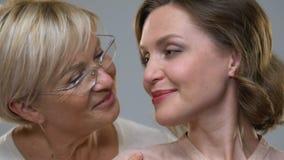 Twee vrouwen die van verschillende leeftijden bij camera, skincare op leeftijd glimlachen verandert, close-up stock footage