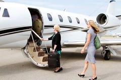 Twee vrouwen die vliegtuig ingaan Stock Fotografie