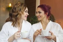 Twee vrouwen die in witte robes thee na kuuroordbehandelingen drinken royalty-vrije stock foto