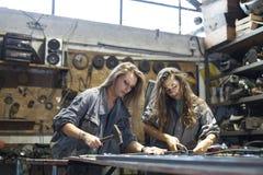 twee vrouwen die in workshop werken stock fotografie