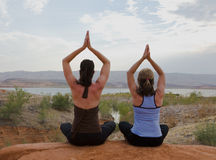 Twee Vrouwen die Yoga doen bij Zonsondergang Royalty-vrije Stock Afbeeldingen