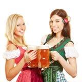 Twee vrouwen in dirndl kleden zich met bier Stock Fotografie