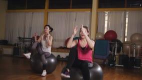 Twee vrouwen doen samen aerobics in de gymnastiek Vrouwen die sportenoefening doen die fitness bal gebruiken stock video