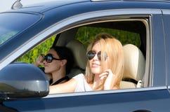 Twee vrouwen in een luxeauto Stock Foto's
