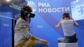 Twee vrouwen gebruikend virtuele werkelijkheidshoofdtelefoon en rond kijkend stock videobeelden