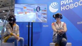 Twee vrouwen gebruikend virtuele werkelijkheidshoofdtelefoon en rond kijkend stock footage