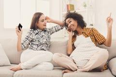 Twee vrouwen het luisteren muziek en het delen van oortelefoons stock afbeelding