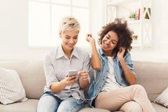 Twee vrouwen het luisteren muziek en het delen van oortelefoons royalty-vrije stock afbeelding