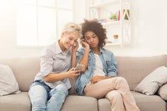 Twee vrouwen het luisteren muziek en het delen van oortelefoons stock foto's