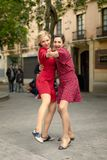 Twee vrouwen in het rode dansen gelukkig omhelst in de straat royalty-vrije stock fotografie