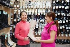 Twee vrouwen kiest hoge laarzen Stock Foto