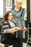 Twee vrouwen kijken catalogus van haarkleuren stock foto