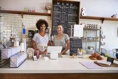 Twee vrouwen klaar om achter de teller bij een koffiewinkel te dienen stock foto