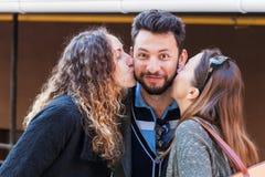 Twee vrouwen kussen in openlucht de mens stock foto's