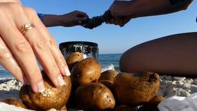 Twee vrouwen maken popatoes met een metaalborstel bij kust schoon stock videobeelden