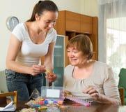 Twee vrouwen maken thuis armbanden stock afbeelding