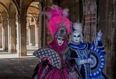 Twee vrouwen in maskers en overladen blauwe en roze kostuums die zich onder de bogen dichtbij de Railto-Brug bevinden, Venetië ti stock fotografie