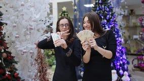 Twee vrouwen met geld in hun handen die op de achtergrond van Kerstbomen dansen stock videobeelden