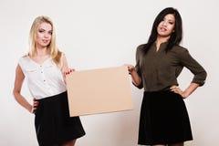 Twee vrouwen met lege raad stock afbeelding