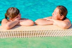 Twee vrouwen ontspannen bij de pool Stock Foto