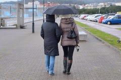 Twee vrouwen op de straat met paraplu's in de regen Royalty-vrije Stock Afbeelding