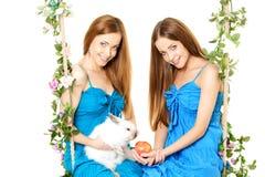 Twee vrouwen op een schommeling op witte achtergrond Royalty-vrije Stock Afbeeldingen