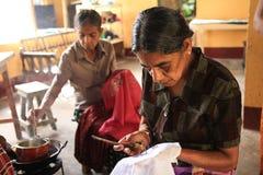 Twee vrouwen overhandigen het schilderen stof stock foto's