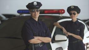 Twee vrouwen in politie eenvormige status dichtbij patrouillewagen en het glimlachen, wet en orde stock videobeelden
