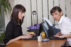 Twee vrouwen roddelen in bureau Stock Afbeeldingen