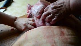 Twee vrouwen snijden een brok van varkensvlees stock videobeelden
