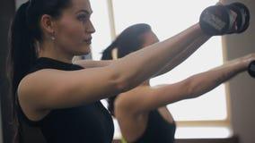 Twee vrouwen in sporten een zwarte passen met een wapenspieren van de domoorschommeling aan stock videobeelden