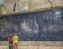 Twee vrouwen staren in le mur des je t'aime in montmartre, Parijs Stock Foto