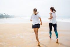 Twee vrouwen stoot de kust op een donkere dag aan Stock Fotografie