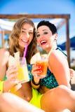 Twee vrouwen in strand versperren het drinken cocktails Stock Afbeeldingen
