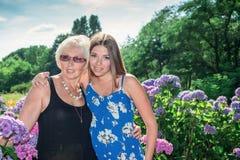 Twee vrouwen van verschillende generaties die zich dichtbij bloemenhydrangea hortensia's bevinden Moeder en dochter Grootmoeder e Royalty-vrije Stock Afbeelding