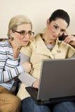 Twee vrouwen werken aan laptop huis Stock Afbeeldingen