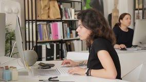 Twee vrouwen werken binnen in bureau naast computers stock videobeelden