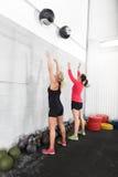 Twee vrouwen werpt geneeskundeballen in geschiktheidsgymnastiek Royalty-vrije Stock Foto's