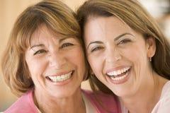 Twee vrouwen in woonkamer het glimlachen royalty-vrije stock foto